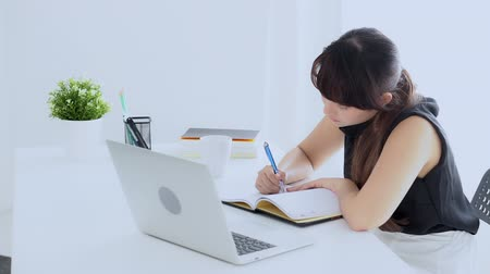 Beautiful young asian woman smiling sitting in the living room study and learning writing notebook and diary at home, girl homework, business woman working with laptop computer on table, education concept.