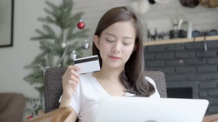 дебет : Beautiful portrait young asian woman shopping online with credit card on laptop computer sitting in living room at home, girl with customer purchase of payment online, lifestyle concept. Стоковые видеозаписи