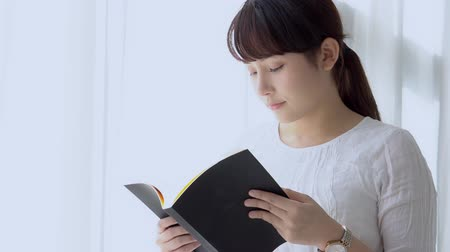 Beautiful portrait young asian woman relax standing learning with reading book for exam in the bedroom at home, girl is student knowledge with study education and lifestyle concept, slow motion.