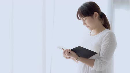 Beautiful portrait young asian woman standing reading book for exam with serious and stress in the bedroom at home, girl is student learning study with fatigue and tension, education concept. Stok Video