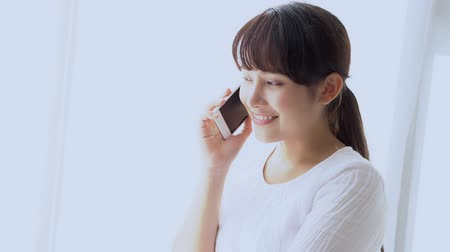 Beautiful young asian woman smiling standing relax in the bedroom, girl using mobile smart phone talking enjoy and fun, communication and social network concept.