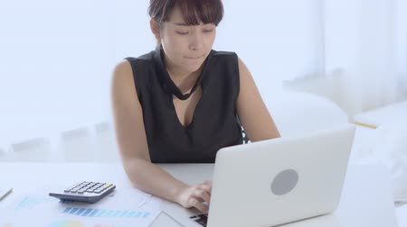 Businesswoman working calculate expenses and typing laptop computer on desk with saving finance, girl pushing calculator for tax, business and finance concept. Stok Video