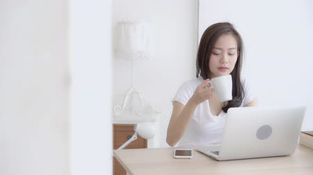 Beautiful young freelance asian woman smiling working and on laptop computer at desk office with professional, girl using notebook and drink coffee, business and lifestyle concept, slow motion.