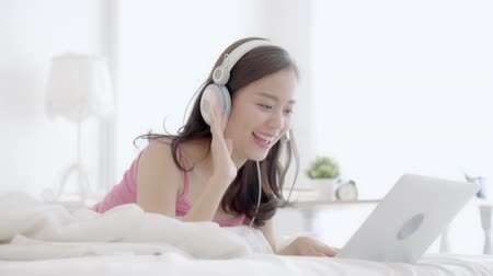 köszönt : Beautiful asian young woman lying on bed using laptop computer showing video call chat in the bedroom at home, girl greet and talking messenger, communication and lifestyle concept.