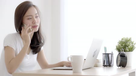 Beautiful young freelance asian woman smiling working on laptop computer and talking mobile smart phone at desk office with professional, girl using notebook, business and lifestyle concept.