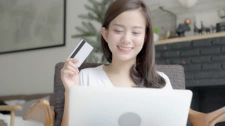 Beautiful portrait young asian woman shopping online with credit card on laptop computer sitting in living room at home, girl with customer purchase of payment online, lifestyle concept. Stok Video