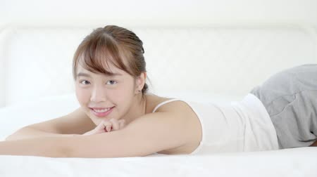 wakeup : Beautiful portrait young asian woman lying and smile while wake up with sunrise at good morning, girl with happy at bedroom, lifestyle and relax concept, slow motion.
