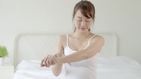 Closeup beautiful young asian woman sitting on a bed stroking hand with soft smooth skin in the bedroom, girl applying body cream and lotion with treatment care, healthy and wellness concept. Stok Video