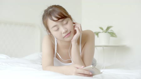 Beautiful portrait young asian woman lying happy earphone listening music with relax and enjoy in the bedroom, girl fun headphone with playing song smart mobile phone, lifestyle concept, slow motion. Stok Video