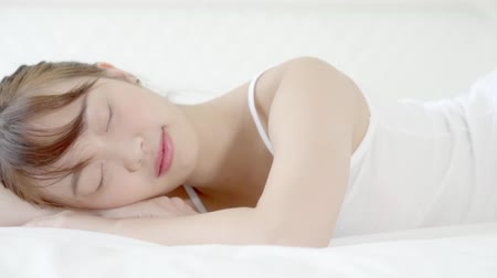 wakeup : Beautiful asian young woman sleeping lying in bed with head on pillow comfortable and happy in the bedroom moving panning camera. girl with relax and leisure for health concept, slow motion.