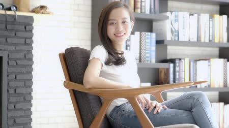 Beautiful portrait young asian woman sitting on chair with smile and happy at living room, moving panning camera, girl with confident relax with happiness looking at camera, lifestyle concept, slow motion.