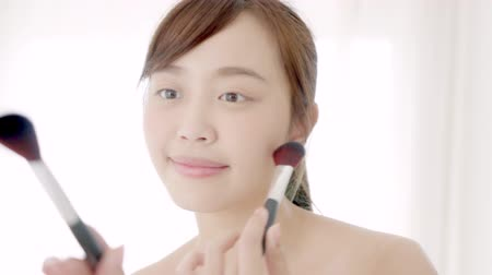 Beauty portrait young asian woman smile with face looking mirror applying makeup with brush of cheek in the bedroom, beautiful asia girl healthy holding blusher, skin care and cosmetic concept.
