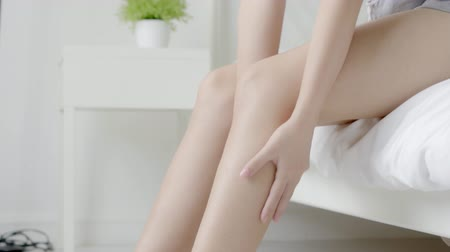 Closeup beautiful young asian woman sitting on a bed stroking legs with soft smooth skin in the bedroom, girl applying body cream and lotion with treatment care, healthy and wellness concept. Stok Video