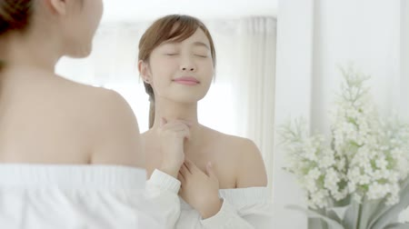 Beautiful young asian woman looking mirror and apply lotion sunscreen with neck, beauty asia girl perfect with skin care and health with cream treatment and moisturizer, wellness and health care concept.