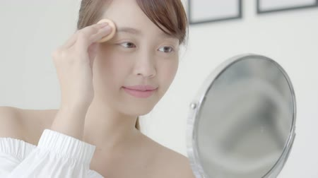 marnost : Portrait beautiful young asian woman applying powder puff at cheek makeup of cosmetic looking mirror, lifestyle of beauty  girl with skin face smile in the bedroom, health and wellness concept.