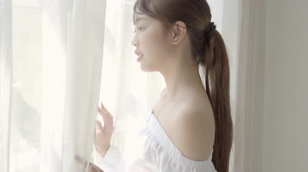 Beautiful portrait young asian woman looking out of window in bedroom at morning after wake up, girl relax with smiling and happy, lifestyle concept, slow motion.