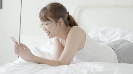 Beautiful portrait young asian woman smiling lying look smart mobile phone reading social network with enjoy on bed at bedroom, girl chat messaging to internet online, communication concept.
