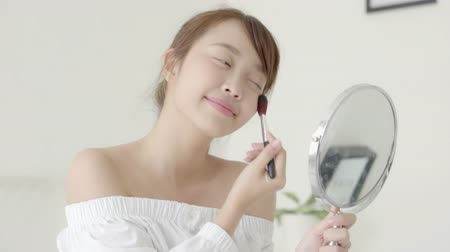 arcszín : Beautiful young asian woman applying powder with brush looking mirror, beauty girl makeup face with blush cosmetic, facial with skin care and health concept.