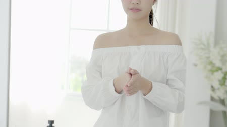 Beautiful young asian woman makeup and cosmetic stroking hand with soft smooth skin in the room, girl applying body cream and lotion with treatment care, healthy and wellness concept. Stok Video