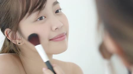 Beauty portrait young asian woman smile with face looking mirror applying makeup with brush of cheek in the bedroom, beautiful of girl holding blusher, skin care and cosmetic concept.