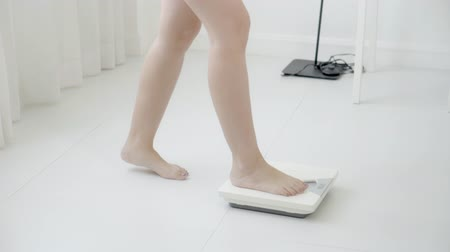 female measurements : lifestyle activity with leg of woman walking measuring weight scale for diet, closeup feet of girl slim weighing measuring for food control, healthy care and wellbeing concept.