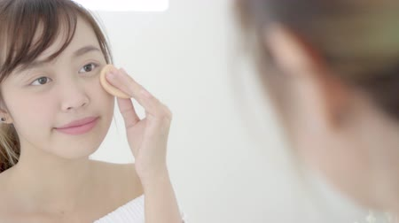 kompakt : Portrait beautiful young asian woman applying powder puff at cheek makeup of cosmetic looking mirror, lifestyle of beauty  girl with skin face smile in the bedroom, health and wellness concept.