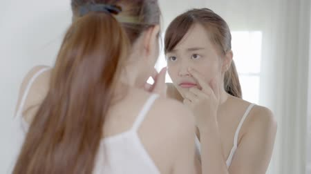Beautiful portrait young asian woman looking the mirror and touch face is a acne, zit treatment, girl problem beauty and skin, perfect with wellness in the bedroom at home with skin care and health concept. Stok Video