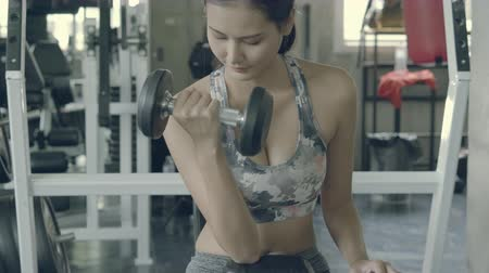 Beautiful young asian woman training workout with strong at gym, asia girl bodyweight with lifting dumbbell at fitness, female strength with exercise for diet, wellbeing and healthy concept. Stok Video