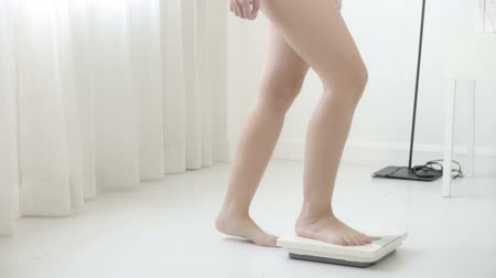 perda de peso : lifestyle activity with leg of woman walking measuring weight scale for diet, closeup feet of girl slim weighing measuring for food control, healthy care and wellbeing concept.