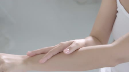 perfektní : Closeup beautiful young asian woman makeup and cosmetic stroking hand with soft smooth skin in the room, girl applying body cream and lotion with treatment care, healthy and wellness concept.