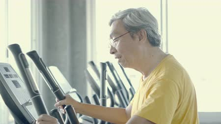 Senior man asian workout in the gym, elder caucasian do activity exercise for cardio in fitness for healthy on elliptical machine, lifestyle and wellbeing, recreation health and care concept.