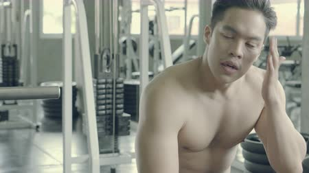 Handsome asian man have muscular after workout with tired and exhaustion in the gym, male have sweat resting break after exercise with strong at fitness, bodybuilding for healthy and wellbeing.