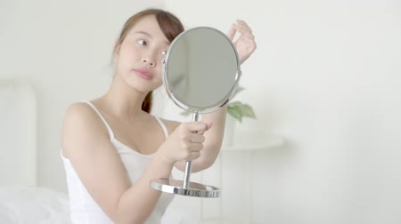 Beauty portrait young asian woman smiling look at mirror of checking skin care caucasian with wellness in the bedroom, beautiful girl happy face for health, lifestyle and wellbeing concept.