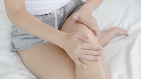 lotion : Closeup beautiful young asian woman sitting on a bed stroking legs with soft smooth skin in the bedroom, girl applying body cream and lotion with treatment care, healthy and wellness concept. Stock Footage