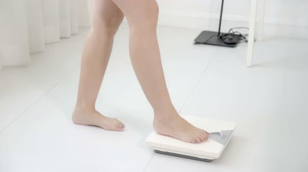 gevşek : lifestyle activity with leg of woman walking measuring weight scale for diet, closeup feet of girl slim weighing measuring for food control, healthy care and wellbeing concept.