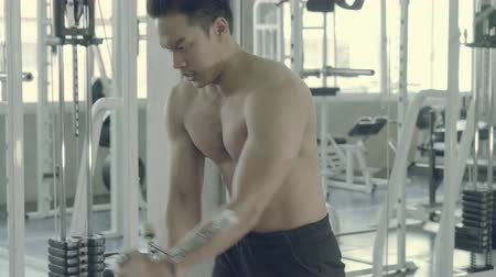 pulling rope : Young asian man doing cable rope triceps pull up exercise for bodybuilding in the gym, asia male effort workout and sport training for exercise muscle with strength, healthy and wellness concept. Stock Footage
