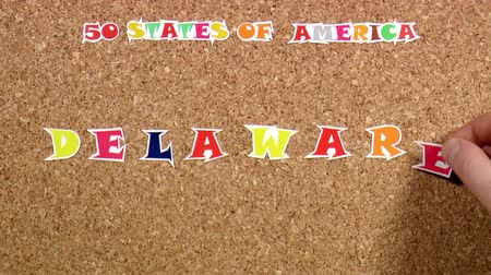 rajzszeg : Video shows word Delaware is one of the states of America on the cork Stock mozgókép