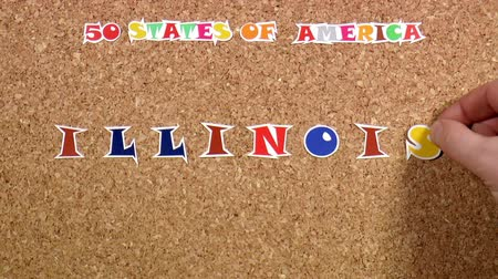 rajzszeg : Video shows word Illinois is one of the states of America on the cork Stock mozgókép