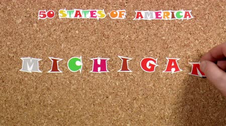rajzszeg : Video shows word Michigan is one of the states of America on the cork Stock mozgókép