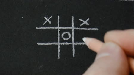 tık : The video shows tick-tack-toe. White pencil on a black paper background