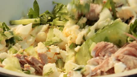 Video shows woman mixes mayonnaise with ingredients for a salad. Meat salad with greens and mayonnaise