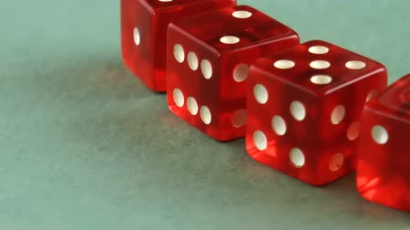 Red glass dices rendered on green background. Close up rotation