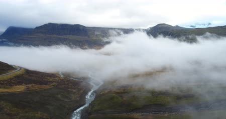 Cinematic aerial view to the clouds from an Iceland mountain