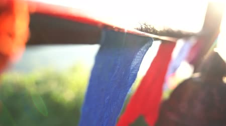 Close up of buddhist prayer flags blowing in the wind at sunrise in a temple in Sri Lanka. Slow Motion Footage. Shallow depth of field,