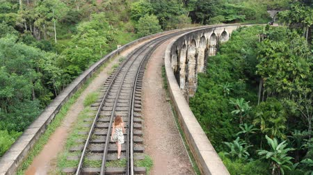 Aerial shot of a girl walking along the railway tracks in a bridge of SRI LANKA. Shot in 4k Stock Footage