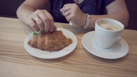 голодный : breakfasts in a cafe with a croissant sandwich with boiled pork and drinking coffee. 4k, HD, close-up.