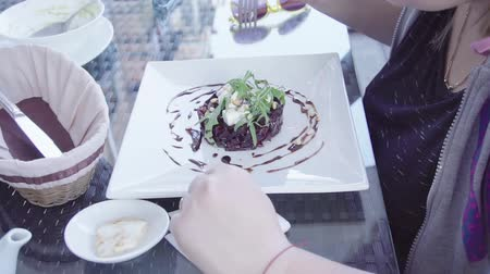 grated : girl eats beet salad with feta and pine nuts on a summer terrace in a cafe, HD Stock Footage