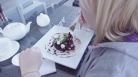 burak : girl eats beet salad with feta and pine nuts on a summer terrace in a cafe, HD Wideo