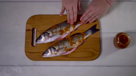carne : 4K, Cooking of three sea bass on white table. Cook preparing fresh fish for baking.