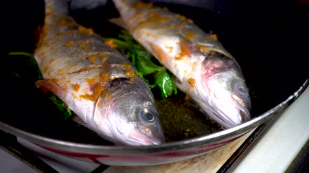 spigola : A chef cooks a Sea bass in frying pan.cooking concept. 4k, seafood